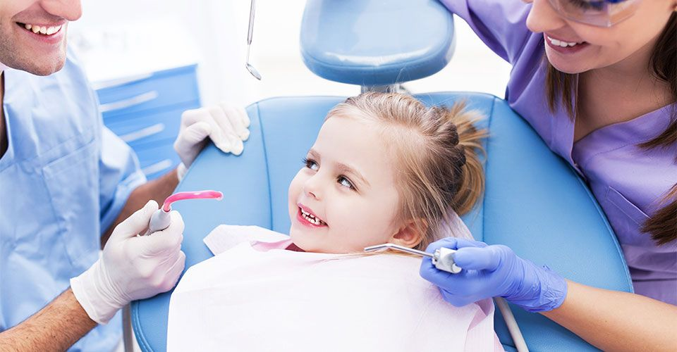 toddler in dentist chair smiling