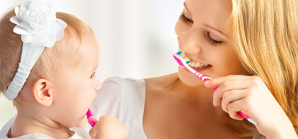 mom brushing with baby